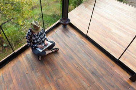 Casual gekleed persoon zittend op de houten vloer van de Rural Bungalow en werkomstandigheden op Laptop
