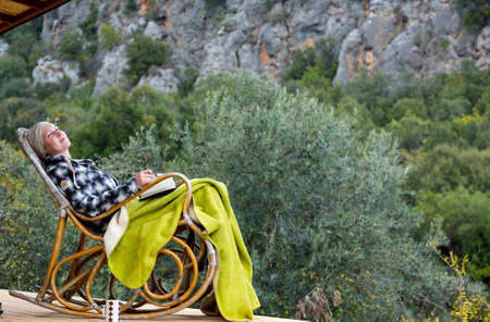 rocking chair: Woman relaxing on Vintage rocking Chair at Balcony of wooden rural Bungalow Forest and Mountains on background