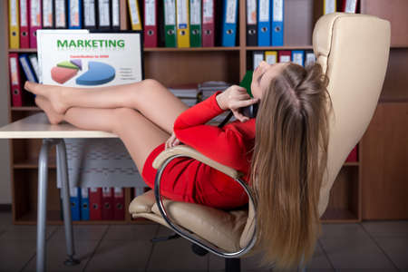 feet on desk: Young Business Woman talking on Telephone at Office lying in Executive Class Leather Chair putting her sexy feet up Table Computer Marketing Chart