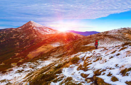 conquering adversity: Walking Hiker in Red Jacket with Backpack on Snow Slope distant Mountain Ridges stacked on Background