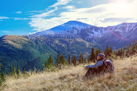 Female Hiker with Backpack sitting on yellow grassy Meadow enjoying warm Sunlight and looking at scenic Mountains View