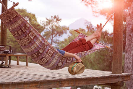 Person relaxing lying in Hammock at rural cottage garden female legs green flora and wooden hut on background Stockfoto