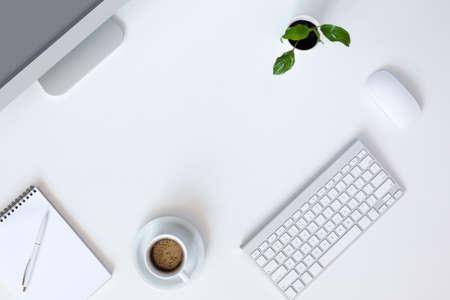 psací stůl: Pohled shora na moderní technologie práce místo na bílém kancelář s velkým stolním počítačem kávový hrnek klávesnice a myš zelená květinové poznámkový blok a pero Reklamní fotografie