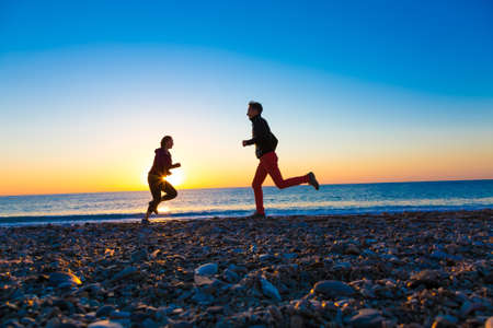 Silhouettes of Man and Woman jogging along Sea Beach at Sunrise with intentionally slanted Horizon and deep blue Sky with Copy Space