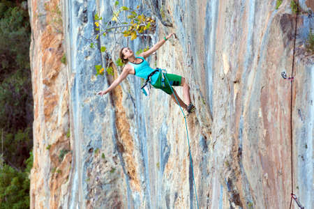 conquest: Extreme Sport Athlete hanging on vertical natural Wall stretching her Hand to reach next Hold bright orange blue stone color