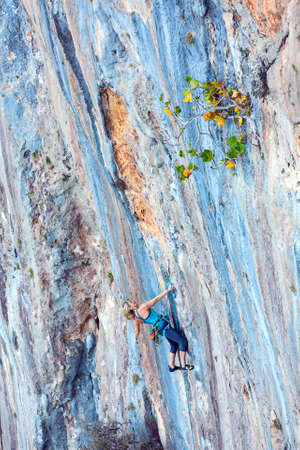 Young Mix Race Female Rock Climber making elegant Move on vertical blue and orange colors Rocky Wall Stock Photo