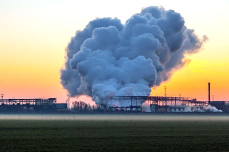 Smoke Stack from Chimney of metallurgical Plant at Sunrise