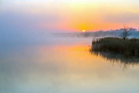 Idyllic View of Morning Fog over Lake and rising Sun Stock Photo