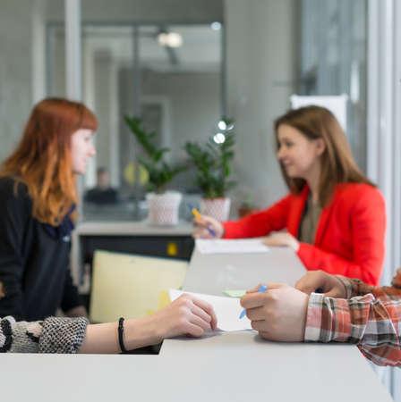 Reception Desk at Office Building Visitors talking to Secretaries