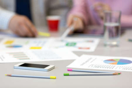 Grey office table with paper charts and stationery
