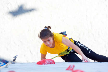 Junior female Athlete makes hard move on climbing wall Editorial