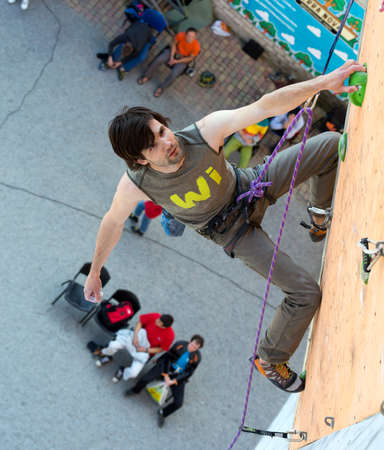 attempt: Climber hanging on climbing Wall at Competitions Editorial