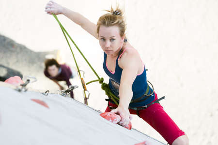 Cute female Athlete hanging on climbing Wall holding Rope