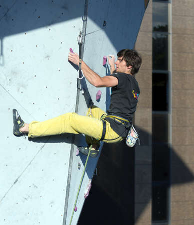 crux: Climber hanging on climbing Wall at Competitions Editorial