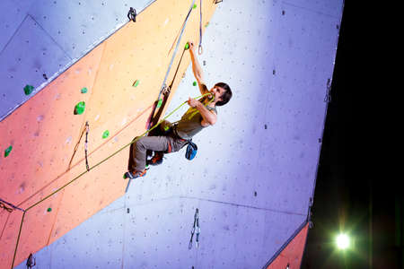 crux: Climber trying fix a rope on Climbing Wall