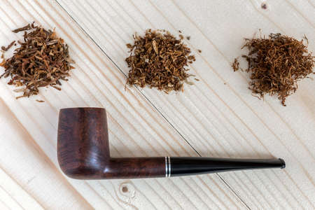 Three different sorts of Tobacco and Pipe on wood Background Stock Photo