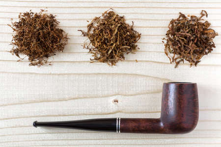 sorts: Three different sorts of Tobacco and Pipe on wood Background Stock Photo