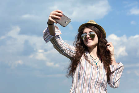 Girl taking self portrait photo on mobile telephone camera Stock Photo
