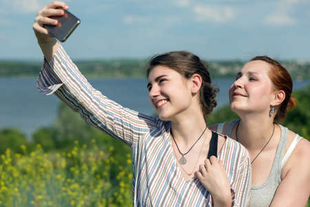 Two People taking self portrait on camera phone outdoors