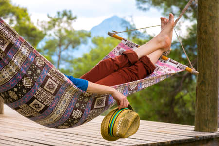 doze: Person relaxing in Hummock holding Travel Hat in Hand at Summer Garden with Forest and Mountains on Background Landscape
