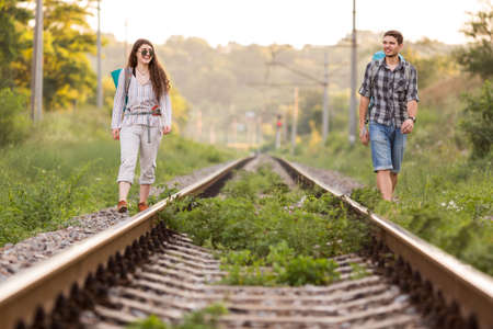 Two young Hikers walking along old Country Railroad