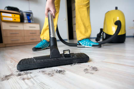 Person cleaning wooden floor with vacuum cleaner