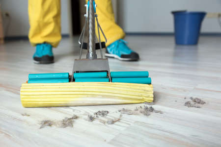 Person washing wooden floor with brush mop