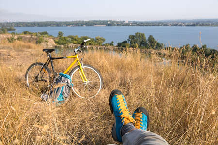 Person in bright sporty Shoes resting on Grass along Bicycle