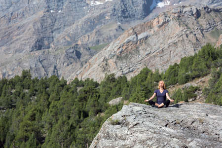 finesse: Mountain and Forest View and Woman doing Yoga Stock Photo