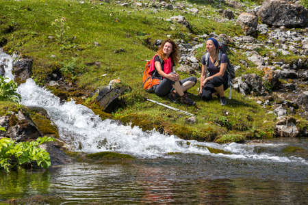 Female Hikers relaxing next to mountain river
