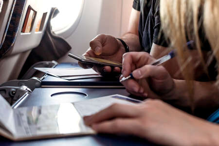 formalities: Passengers filling in Immigration Forms in the Aircraft Stock Photo