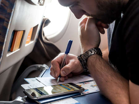 formalities: Bearded pensive Man filling Immigration Form in Aircraft Stock Photo