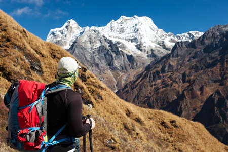 Man with Backpack staying and observing Mountain Scenery