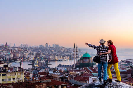 Couple travelling together staying on roof and overlooking cityscape