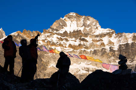 Silhouettes of Mountain Climbers staying against high Peaks Stock Photo