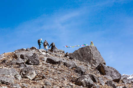Group of Mountain Climbers approaching to rocky Summit with buddhist Flags