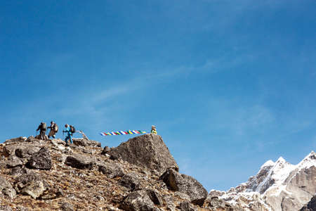 Mountain Peak with buddhist prayer Flags and Climbers walking