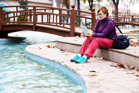Cute Woman sitting in Park reading tablet device