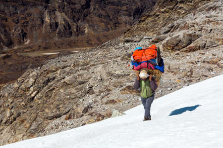 Nepalese Porter carrying Basket with luggage of mountain expedition