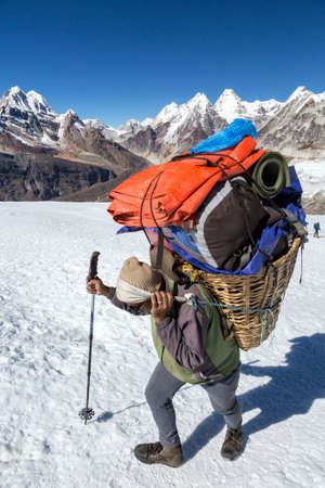 Nepalese Sherpa Porter walking on Glacier with trekking Pole carrying Basket with lots of Mountain Expedition Luggage using traditional Head Strap in Himalaya