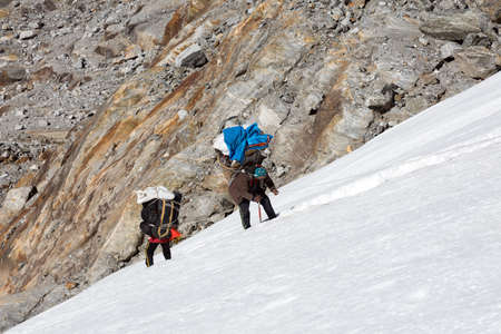 Nepalese Mountain Porters climbing Glacier carrying heavy Luggage Stock Photo