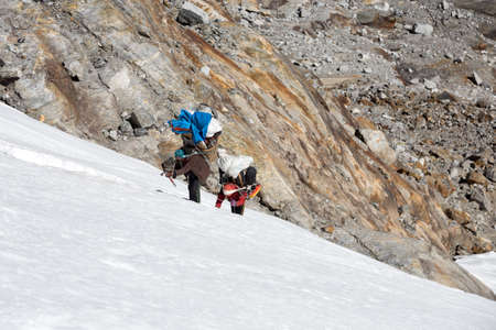 Nepalese Mountain Porters climbing Glacier on steep Ice Wall Stock Photo