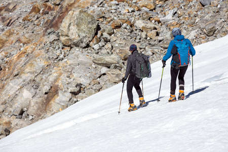 belay: Mountain Climbers Man and Woman walking on steep Ice Slope