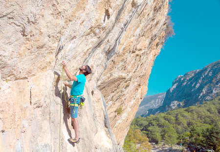 Mature male Climber making Move on vertical Rock Stock Photo