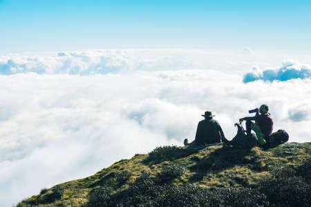 People resting on Mountain Cliff enjoying top cloud Sky Horizon Stock Photo