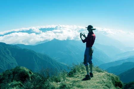 Person taking Photo Mountain Scenery on Camera Phone Stock Photo