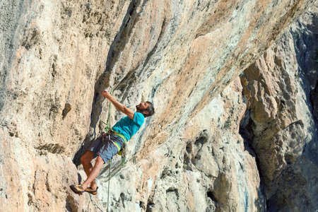 real leader: Mature male Climber making risky Move on dangerous Rock