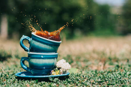 Two blue ceramic cups on the grass with a splash of coffee decorated with summer flowers Stock Photo