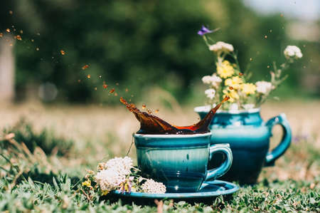 milkman: blue ceramic cups with a milkman on the grass with a splash of coffee decorated with summer flowers