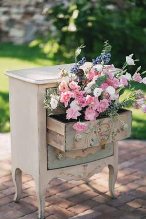 A vintage beige bedside table stands outside in the summer, decorated with a bouquet of pink roses flowers Stock Photo